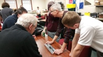 The build team discussing the arms of the robot